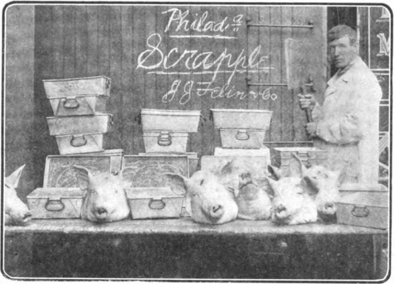 "A black and white photograph of a man in white clothing standing to the right of a table filled with metal containers and hog heads. Written in chalk on a wooden surface behind the containers and heads are the words ""Philadel Scrapple, J. J. Felin & Co."