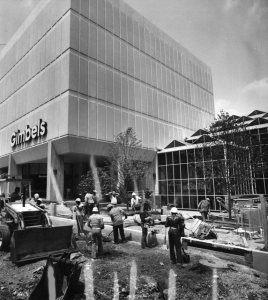 A black and white photograph of a construction crew outside of the glass and steel building, working on the sidewalk and road.
