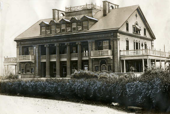 A sepia-tone photograph of a two story building surrounded by fields and bushes. The building is rectangular, with a peaked roof, pillars near the middle of the building, and a balcony on the end of the building.