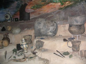 A color photograph of a variety of clay pots, jewelry, stone tools, metal tools, and other metal items are on an uneven brown landscape.