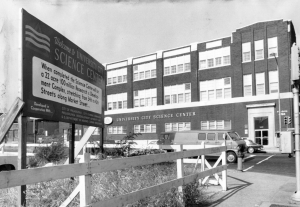 A black and white photograph of the a three story building with the words