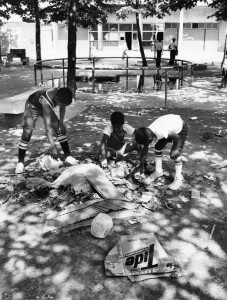 A black and white image of three children picking through a pile of trash in the middle of a playground. the side of an apartment building and playground equipment is in the background of the image.