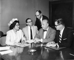 An image of a groupd o five people sitting around a desk, looking at paperwork. There are four men with suits, and one woman in a dress.