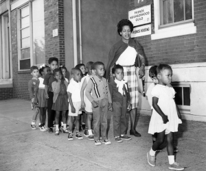 A black and white photograph of a woman walking with a group of children down a sidewalk, outside of a brick building.