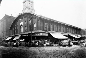 A black and white photograph of a building with a large tower at the front of the rectangular building. There is an overhang covering the sidewalk along the building, and the sidewalk is filled with people and products.