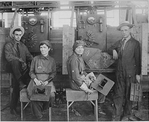 A black and white photograph of two women sitting with welding equipment and two men in suits with clipboards. There is a large industrial machine behind the group, and each person is starring at the camera.