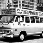 A black and white photograph of a van covered in signs and lettering parked on the street. the main sign on top of the van reads