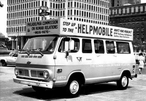 "A black and white photograph of a van covered in signs and lettering parked on the street. the main sign on top of the van reads ""Step up to the Helpmobile."""
