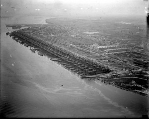 A black and white photograph from an aerial view of a large shipyard on the edge of the Delaware river. There are large scaffolding that surround boats under construction, and rows of buildings covering the land.