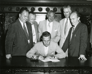 A black and white photograph of a man signing a document at a desk with a group of five men standing behind the signer.