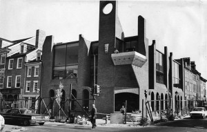 A black and white photograph of a brick building with architectural designs that are not found in the adjacent row houses There is construction equipment outside like ladders and scaffolding in front of the modern building.
