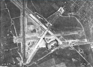 A black and white aerial photograph of the Philadelphia Municipal Airport, showing main building, runways, and fields surrounding the land.