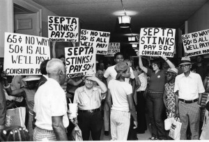 A black and white photograph of people standing in a hall way, holding protest signs. The group of people fills the hallway, and most of the people are wearing casual clothes. In the foreground of the image are some people with their backs turned to the camera.