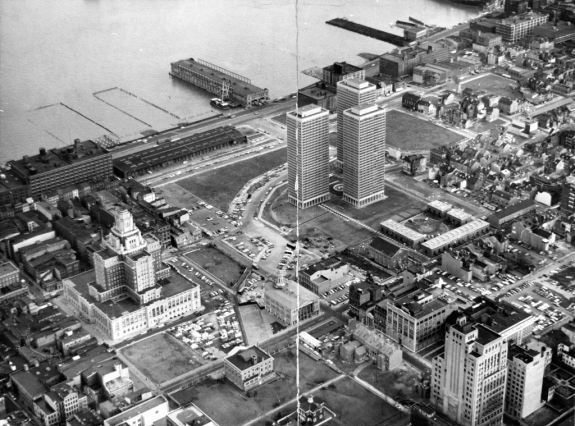 A black and white aerial image of the Society Hill area of Philadelphia. The image shows three large residential towers in the center, with row houses to the around the edges of the image, with a part of the Delaware river towards the top of the image.