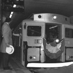 A black and white photograph of a man looking at the end of a subway car as it is leaving an underground subway terminal. The man is wearing a jacket, holding a hat, and standing by a large concrete pole that has a sign on it reading: