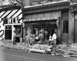 A black and white photograph of a group of people (mostly younger people) standing next to a vandalized storefront. Pieces of debris are covering the ground of the store.