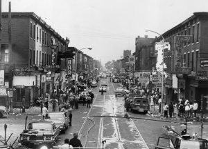 A black and white photograph showing the street of Columbia Avenue, with people, cars, and storefronts down the street visible.