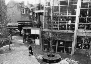 A black and white image of a modern building with glass walls and steel construction. There is a courtyard in the foreground of the and a person is walking through it. In the background of this image are brick row houses.