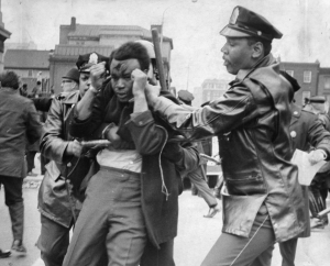 A black and white photograph of a man with blood on his face and hands by his head surrounded by two police officers holding batons.