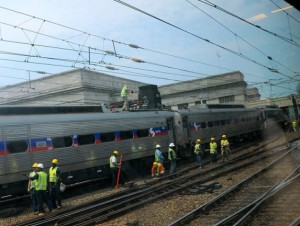 SEPTA employees work on a commuter train that was stuck on the track because of overhead wire problems