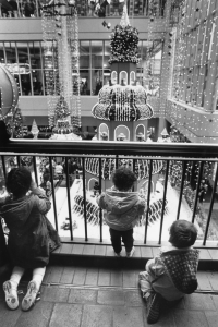 A black and white photograph of children looking through a railing to view a Christmas display below them. There is a tower with lights and fake snow on it in the background of the image.