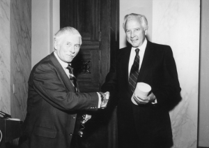 A black and white photograph of two men shaking hands. The man on the right is holding an award.