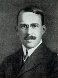 A black and white photograph of a man from the shoulders up, in a suit with glasses and a mustache looking directly at the viewer.