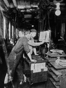 A black and white photograph of two workers in a cluttered factory looking at a time sheet.