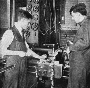 A black and white photograph of two men in overalls looking at a machine in a production shop. The man on the left of the image is holding a stopwatch.
