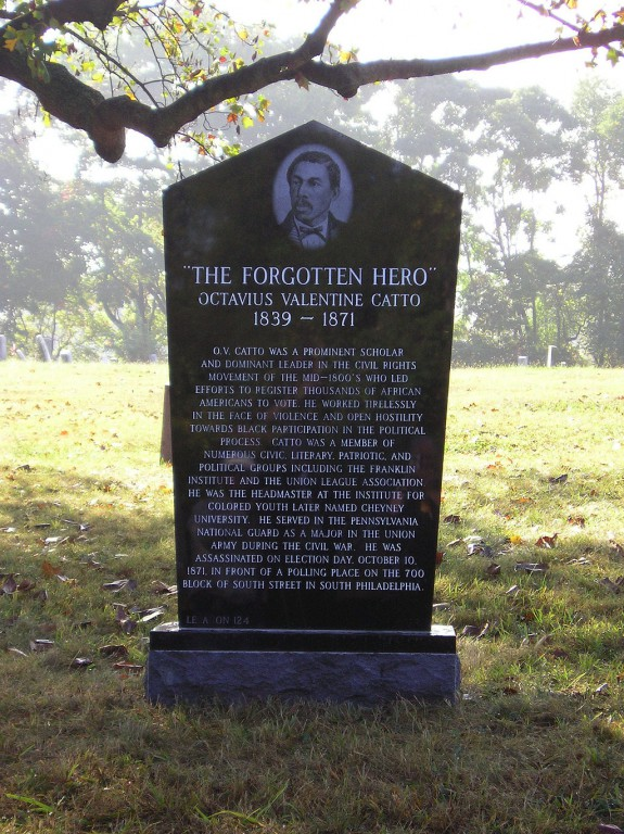 A color photograph of a black grave stone in the middle of a field. The stone has an engraving of a man at the top and a long epigraph covering most of the side facing the viewer. Some grass, leaves, and trees are visible.
