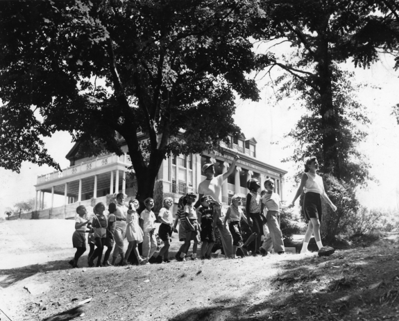 A black and white photograph of children walking through a field in front of a building, with some trees off surrounding the group.