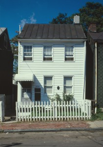 A color photograph of a two story white house, with a small white fence in front of it. Parts of the sidewalk and street are shown in front of the property.
