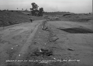 A photograph of some leveled dirt with markers and rope showing the edges of a road. Hills of dirt and people are in the background.