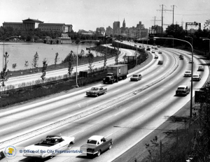 A black and white photograph of a highway with cars as it curves towards Philadelphia. Buildings, city hall, and the Philadelphia museum of art are in the background.