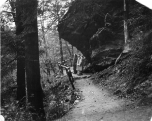 A black and white photograph of three people standing on a trail below a rock ledge in the forest.
