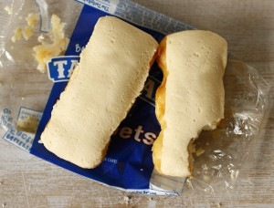 A photograph of two butterscotch krimpets, unwrapped and set in their wrapper