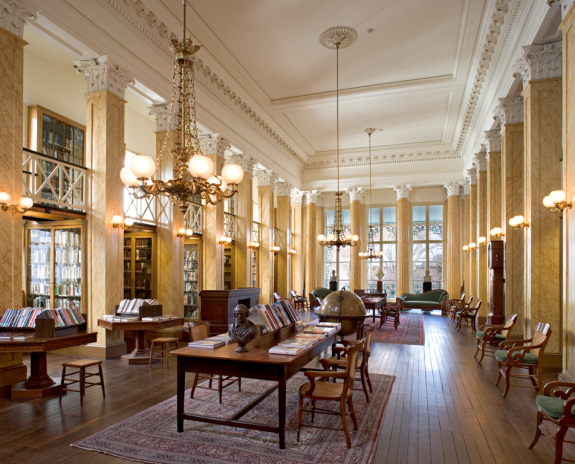 A color photograph of a reading room of a library. The ceiling is high, with elegant lights, furniture, and art decorating the room.