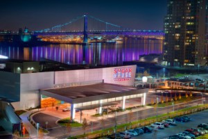 A view of the SugarHouse Casino at night with the Ben Franklin Bridge in the background.
