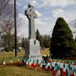 color photograph of a large celtic cross shaped headstone, surrounded by 57 Irish flags and a large plaque on the ground directly in front of it
