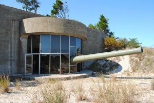 A color photograph of a stone buildings with a curved window, and a large barrel gun sticking out of the window. The building is surrounded by grass, sand, and some trees in the background.
