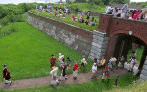 A color photograph of re-enactors walking out of a walled fort. Onlookers are sitting on  the wall and standing in the background.