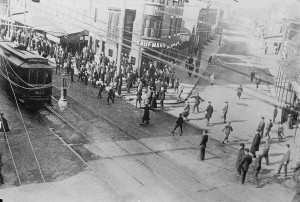 A group of strikers throw stones at a passing trolley car.