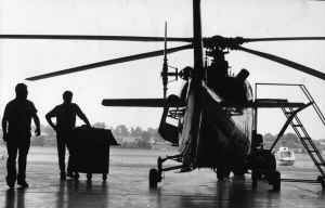A black and white photograph of two people next to a helicopter near the northeast Philadelphia airport.