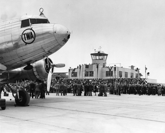 A black and white photograph of the exterior of an airport, with a large crowd of people and an airplane in the foreground.