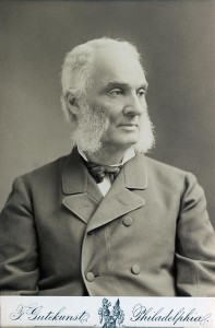 A black and white photograph of man from the chest up, wearing a jacket and a tie.