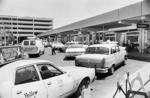 A black and white photograph of taxis and cars in front of an air port terminal.