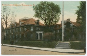 A color postcard of the corner of a city block, with some buildings and trees in the background. Some steps and a light pole are in the foreground and some people are walking on the sidewalk.