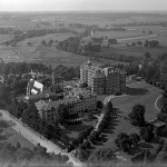 A black and white aerial photograph of three large, multi-story buildings in the middle of a tree grove.