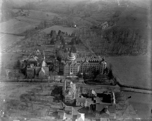 A black and white aerial photograph of a series of school buildings surrounded by fields and sections of trees.