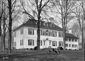 A black and white photograph of the front of a house, with trees and a cannon in the foreground.